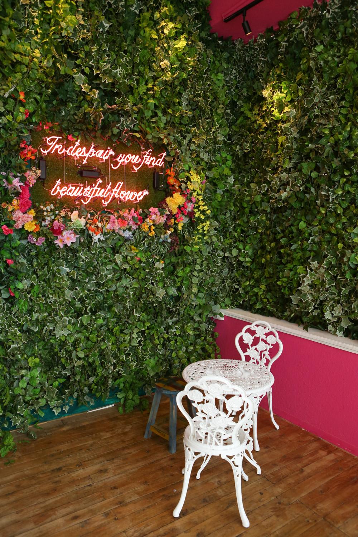 壁一面に造花をあしらったガーリーな席
