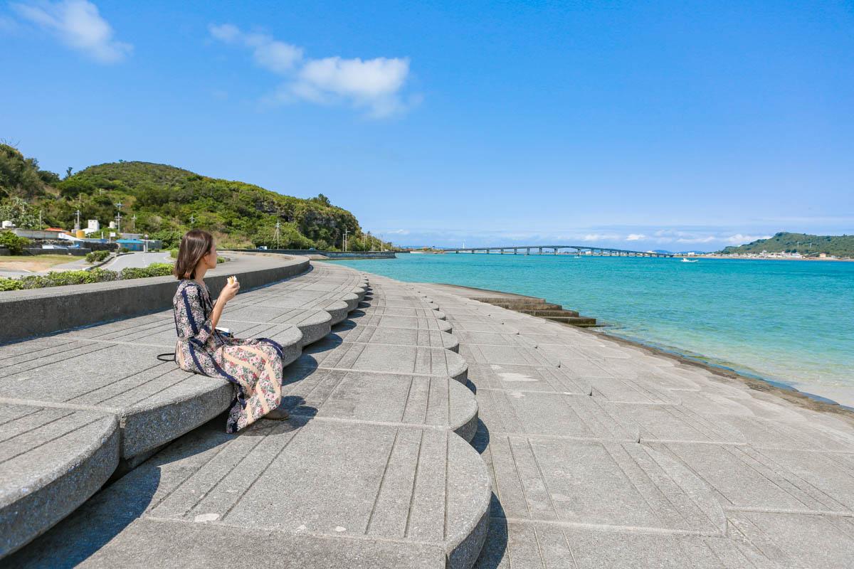 海岸前の階段で軽食を食べる女性