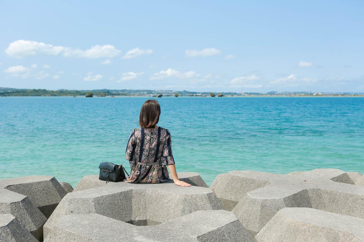防波堤に腰掛ける女の子