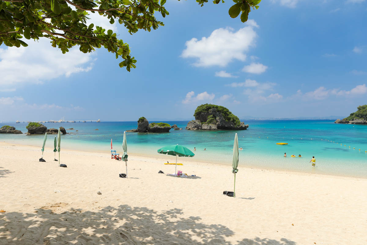 パラソルが並んだエメラルド色の浜